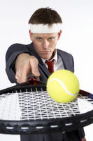 Businessman balancing a tennis ball on the racquet
