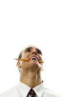 Businessman biting a pencil while thinking