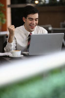 Businessman cheering while using laptop