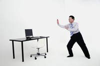 Businessman doing tai chi in his office