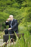 Businessman drinking coffee in a park