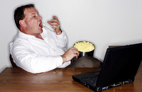 Businessman eating popcorn while working on his laptop