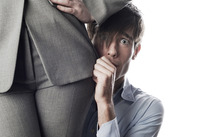 Businessman hiding behind businesswoman
