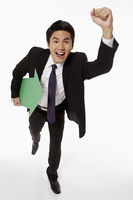 Businessman holding a green arrow and running