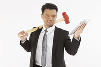 Businessman holding a hammer and a digital tablet