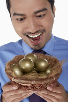 Businessman holding a nest filled with golden eggs