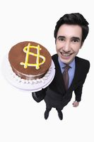 Businessman holding cake with dollar sign