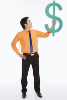 Businessman holding up a dollar sign