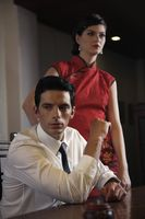 Businessman in deep thought, woman in cheongsam standing beside him