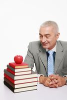 Businessman looking at apple on a stack of books