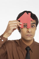 Businessman looking through a cut out house