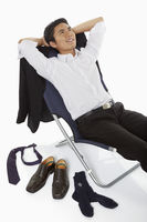 Businessman lying on a chair, smiling