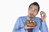 Businessman putting golden egg close to ears
