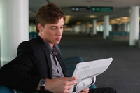 Businessman reading newspaper in airport lounge