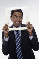 Businessman smiling and looking through cutout paper frame