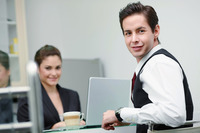 Businessman smiling, businesswoman using laptop in the background