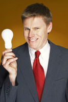 Businessman smiling while holding a light bulb