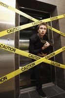 Businessman sneaking out of a cordon taped elevator