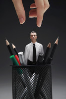 Businessman standing amongst stationery in the pencil holder