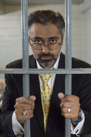 Businessman standing behind prison cell bars