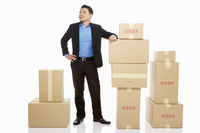 Businessman standing beside a stack of cardboard boxes