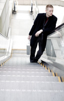 Businessman standing on an escalator