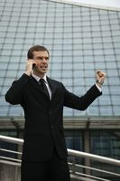 Businessman talking on mobile phone and shaking his fist