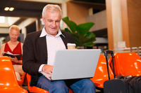 Businessman using laptop in airport lounge, businesswoman with organizer in the background