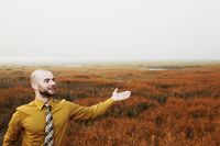 Businessman with arm outstretched, green field in the background