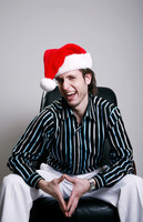Businessman with christmas hat sitting on the chair laughing
