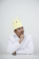 Businessman with crown looking up while thinking