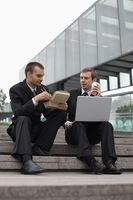 Businessmen eating while working outdoors