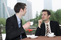 Businessmen enjoying coffee at outdoor cafe