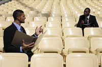 Businessmen having discussion in a stadium