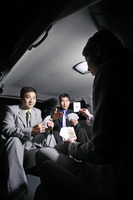 Businessmen playing cards in the car