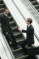 Businessmen talking on escalator