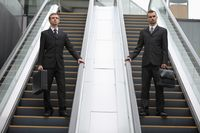 Businessmen with briefcase standing on escalator