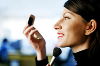 Businesswoman applying makeup
