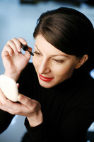 Businesswoman applying mascara