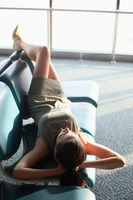 Businesswoman asleep on seats in airport lounge