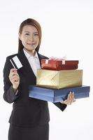 Businesswoman carrying a stack of gift boxes and holding a credit card