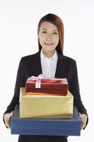 Businesswoman carrying a stack of gift boxes