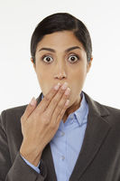 Businesswoman covering mouth with hand