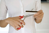 Businesswoman cutting credit card