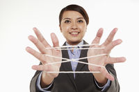 Businesswoman forming a cat's cradle