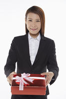 Businesswoman handing out a gift box