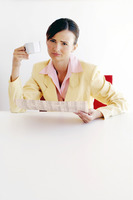 Businesswoman holding a cup of coffee and a newspaper