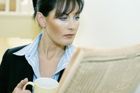 Businesswoman holding a cup of coffee while reading newspaper