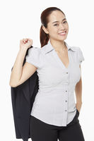 Businesswoman holding a jacket and smiling