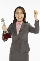 Businesswoman holding a trophy and cheering